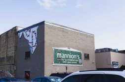 Mannion's sign with a trompe l'oeil painting of fabric.